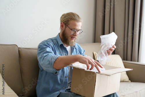 Vászonkép Happy man customer unpacking cardboard box receive open post mail delivery package