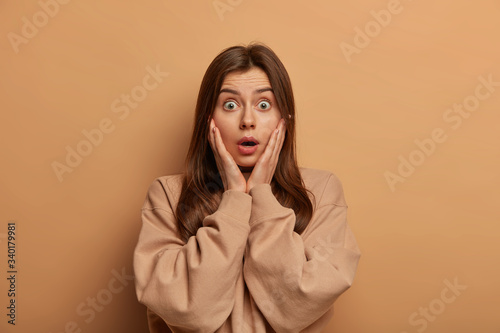 Fényképezés Shocked speechless woman gasps from amazement and grabs face, reacts impressed at gossip, hears astounding rumor, has bugged eyes, wears sweatshirt, poses against brown background