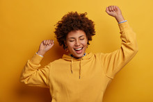 Carefree Energetic Dark Skinned Young Woman Dances With Hands Up, Sings Favorite Song, Triumphs Over Win, Closes Eyes, Expresses Happiness, Achieves Victory Or Approval, Wears Yellow Sweatshirt