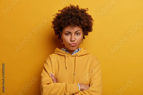 Fotografia Skeptic angry ethnic woman expresses suspision, stands with arms folded, pouts l