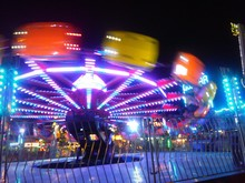 Blurred Motion Of Illuminated Amusement Park Ride Against Sky At Night