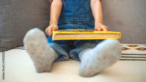 Photo Shot of an adorable little boy reading a book while relaxing on the sofa at home