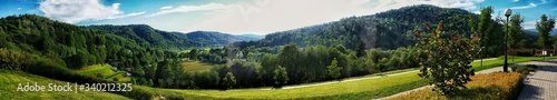 Panoramic View Of Green Landscape And Mountains During Sunny Day - fototapety na wymiar