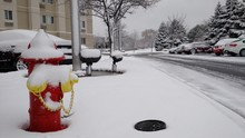 Fire Hydrant On Snow Covered Sidewalk In City
