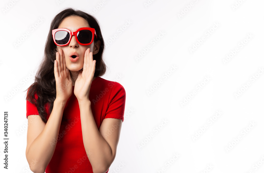 Fototapeta Portrait excited beautiful woman wearing retro red sunglasses. Surprised young female look telling something. She get happy, announce that product on sale, discount in summer time. isolated on white
