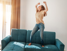 Happy Young Woman In A T-shirt And Jeans Dancing On A Blue Sofa In The Living Room At Home, Buying Real Estate And Furniture Concept