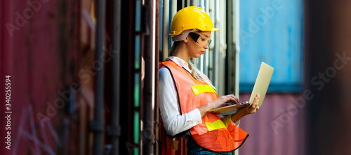 Fotografiet Portrait of Women worker use laptop computer for control loading Containers box from Cargo at container yard