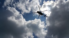 Low Angle View Of Helicopter Flying Against Cloudy Sky
