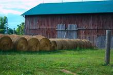 Hay Bales By Barn On Grassy Fi...