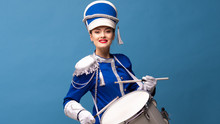 Charming Cheerful Drummer In A Blue Uniform, Sings And Plays The Drum.