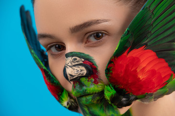 Woman with painted parrot bird on her face. Body art with real wings on the cheeks