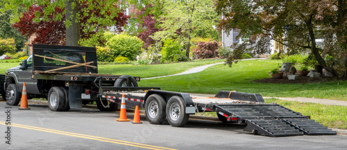 Fototapeta Landscaping truck with empty flatbed trailer with ramp parked on residential neighborhood street