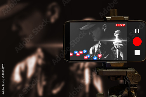 Fototapeta asian music vlogger streaming a live video while singing a song in sound studio obraz