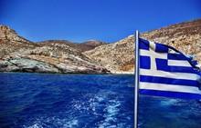 Greek Flag Against Rocky Beach