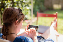 Lazy Day At Home. Sitting Girl Is Enjoying The Day On The Porch, Using Her Smartphone