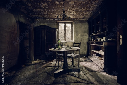 Abandoned room with a table in the middle and shelves against a wall near the wi Canvas