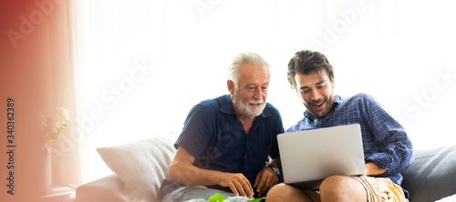 Obraz Father and son family time together at home concept. Smiling old father and happy son sitting on sofa using digital laptop computer in living room at home - fototapety do salonu