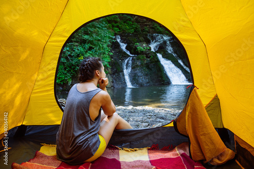 woman sitting in yellow tent looking at waterfall Fotobehang