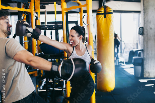 Cuadros en Lienzo Young attractive woman with instructor on kickboxing training
