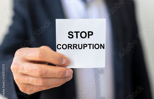 STOP CORRUPTION inscription on a white sticker holding by a man's hand Canvas Print