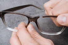 Closeup Of Man's Hands Holding Broken Frame Of Glasses. Young Optometrist Holding In His Hands Recked Eyeglasses Ribs. Professional Repair Of Broken Glasses In Optician Clinic.