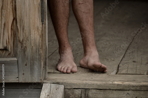 Obraz Low Section Of Barefoot Man On Wooden  Floor - fototapety do salonu
