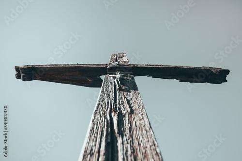 czarno białe zdjęcie starego, drewnianego krzyża z figurami Jezusa Chrystusa na tle nieba