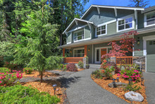 Beautiful Long Two Story Tall Northwest Home Exterior In Grey Green With Spring Landscaping And Large Driveway, Garden And Large Pond Fountain With Rocks.