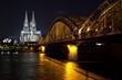 Illuminated Hohenzollern Bridge Over Rhine River Against Cologne Cathedral