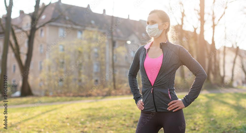 Fototapeta Fit woman during health crisis exercising outdoors wearing mask