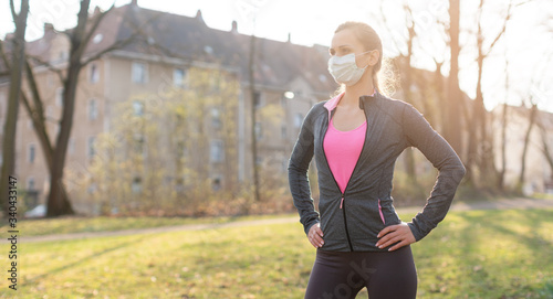 Fototapeta Fit woman during health crisis exercising outdoors wearing mask