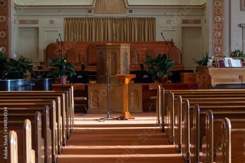 medium wide shot of an empty church sanctuary with afternoon sunlight pouring in Canvas Print