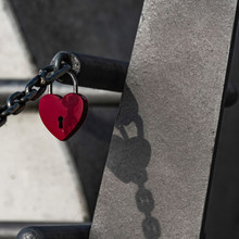 Close-up Of Red Heart Shape Padlock Locked On Chain And Metal