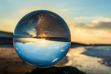 Upside Down Reflection Of Beach On Crystal Ball During Sunset