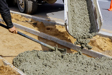 Concrete Being Poured From A Truck Into A Concrete With Sidewalk