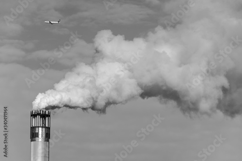 Leinwand Poster Low Angle View Of Airplane Flying Over Smoke Stack Emitting Pollution Against Sk