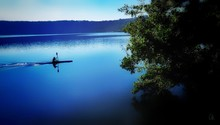 Silhouette Man On Boat In Lake Against Sky