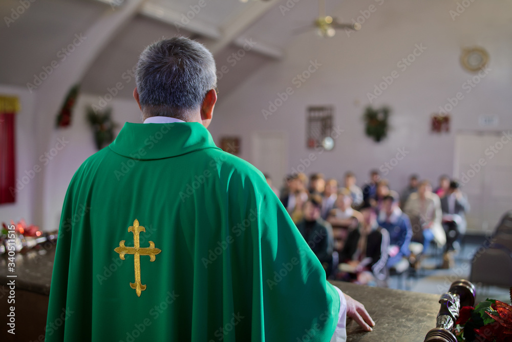 Fototapeta Catholic priest standing on a church podium and preaching, religion