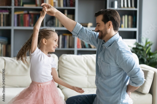 Loving caring father standing on one knee holds little daughter by the hand while she spins Canvas Print