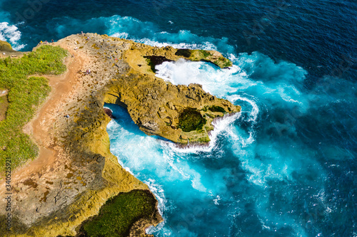 Valokuva Aerial view of spectacular ocean waves from a blue, tropical sea crashing into a