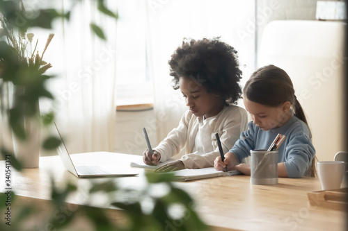 Fototapeta Concentrated small multiracial sisters sit at the desk having online class on laptop, little multiethnic girls siblings study together engaged in web lesson on computer at home, homeschooling concept obraz