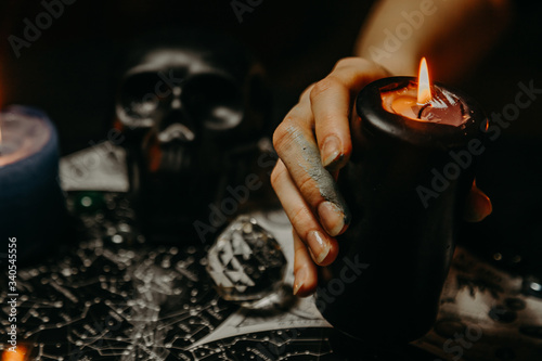 Obraz A witch performs a magic ritual with candles  - fototapety do salonu
