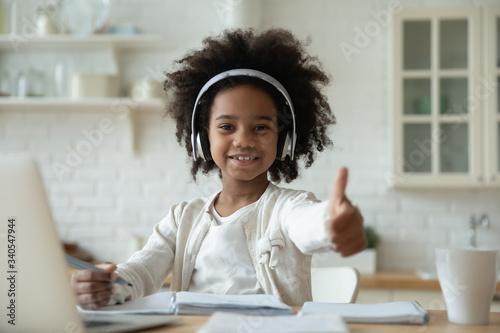 Cuadros en Lienzo Portrait of happy little African American girl pupil in headphones study online