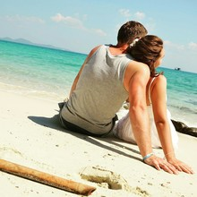 Rear View Of Couple Sitting At Beach