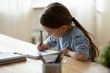 Leinwandbild Motiv Small girl sit at desk writing in notebook studying online do exercises at home, little child handwrite prepare homework on quarantine, have web class or lesson indoors, homeschooling concept