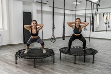 Portrait Of Two Young Pretty Active Girls In Fitness Clothes Doing Exercises For Squatting With Trampoline During Training In Gym