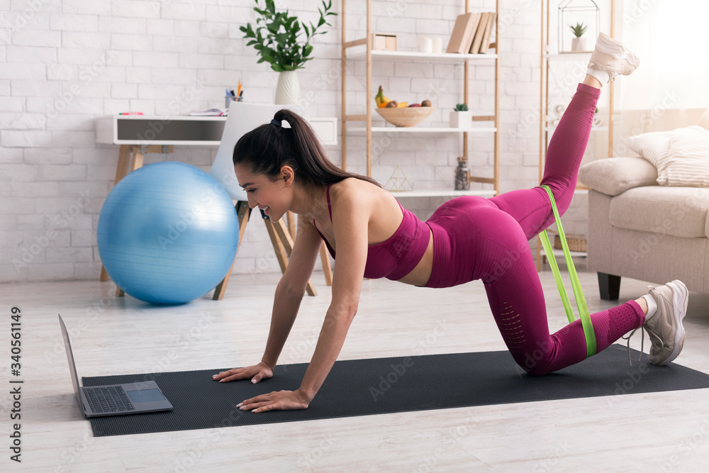 Fototapeta Stay home, stay fit. Cheerful girl working out with elastic band in front of laptop indoors