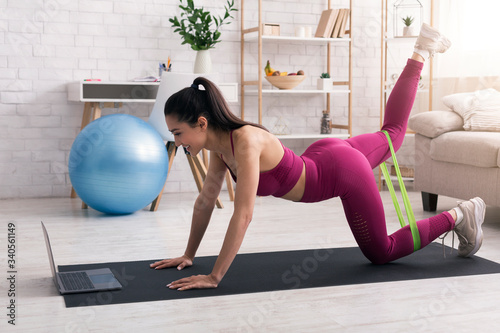 Fototapeta Stay home, stay fit. Cheerful girl working out with elastic band in front of laptop indoors obraz