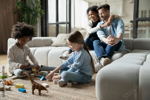 Tablou Canvas Diverse young parents sit on couch in living room watch multiracial daughters pl