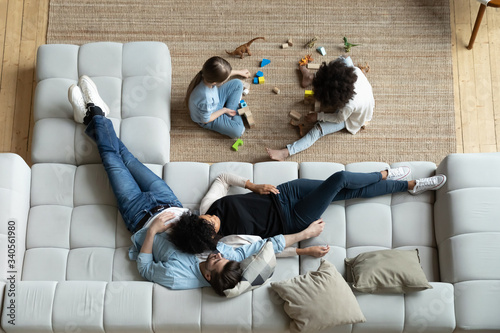 Top view of happy multiethnic young family with small children relax in living room at home together, diverse parents rest on comfortable sofa watch multiracial little daughters play on warm floor